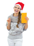 Thoughtful woman and christmas hat holding letter Stock Photography