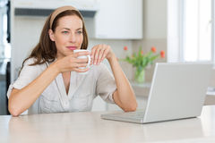 Thoughtful woman with coffee cup and laptop in kitchen Royalty Free Stock Images