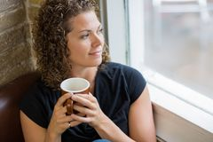 Thoughtful Woman With Coffee Mug In Cafe Royalty Free Stock Photography