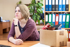 Thoughtful woman with collected in box things Royalty Free Stock Image