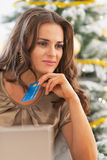Thoughtful woman with credit card and laptop near christmas tree Stock Photography