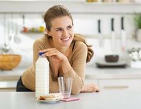 Thoughtful woman with crisp bread and milk in kitchen Stock Image