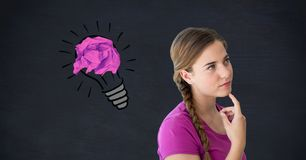 Thoughtful woman with crumpled paper on light bulb shape against black background Royalty Free Stock Photos
