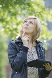 Thoughtful woman with digital tablet looking up Stock Photo