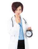 Thoughtful woman doctor holding an alarm clock in her hand, Royalty Free Stock Photo