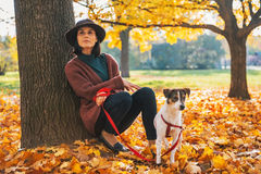 Thoughtful woman with dog outdoors in autumn Royalty Free Stock Images