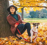 Thoughtful woman with dog outdoors in autumn Stock Images