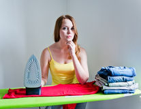 Thoughtful woman of doing the ironing. Stock Photos