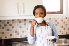 Thoughtful woman drinking coffee. Thoughtful african woman drinking coffee at home Stock Photos