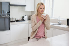 Thoughtful woman drinking coffee in kitchen Stock Photos