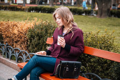 Thoughtful woman drinking coffee and using tablet in park Royalty Free Stock Photography