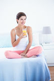 Thoughtful  woman drinking glass of orange juice. At home in the bedroom Royalty Free Stock Images