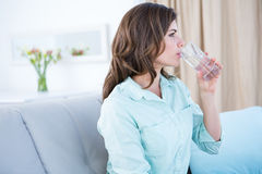 Thoughtful woman drinking a glass of water Stock Photo