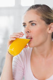 Thoughtful woman drinking orange juice Stock Photos