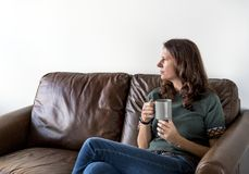 Thoughtful woman drinking tea or coffee. Sitting on a cozy couch Royalty Free Stock Photo