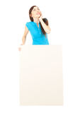 Thoughtful woman with empty poster looking up Stock Images