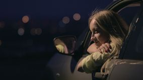 Thoughtful woman enjoying landscape of night city. From open car's window on the observation deck. Dreaming young lady leaning her arms on car's window and stock video footage