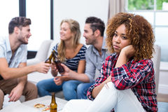 Thoughtful woman with friends enjoying beer in background Royalty Free Stock Image