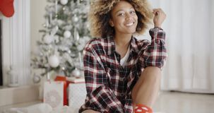 Thoughtful woman in front of a decorated Xmas tree. Thoughtful trendy young African woman sitting on the floor in front of a decorated Christmas tree at home stock video
