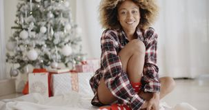 Thoughtful woman in front of a decorated Xmas tree. Thoughtful trendy young African woman sitting on the floor in front of a decorated Christmas tree at home stock footage