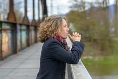 Thoughtful woman gazing out from a bridge. Thoughtful woman gazing out from the railing of a bridge with her thumbs to her mouth and a serious expression on a royalty free stock photos