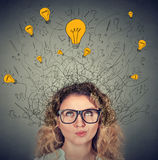 Thoughtful woman in glasses with many ideas light bulbs above head. Looking up  on gray wall background. Eureka creativity concept Royalty Free Stock Photography