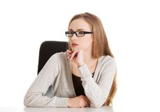 Thoughtful woman in glasses sitting at the desk Stock Image
