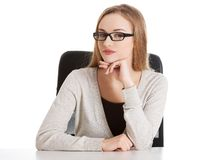 Thoughtful woman in glasses sitting at the desk Royalty Free Stock Photography
