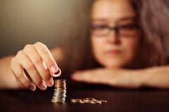 Thoughtful woman with glasses stacking coins on black background. Very shallow depth of field, selective focus on the forefinger a. Nd the coin stack. Personal royalty free stock photography