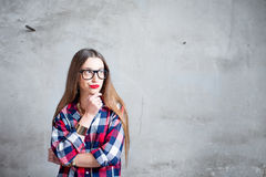 Thoughtful woman on the gray wall background Royalty Free Stock Photography