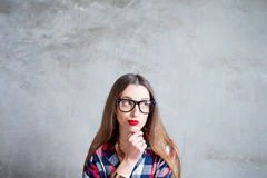 Thoughtful woman on the gray wall background Royalty Free Stock Photos