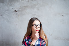 Thoughtful woman on the gray wall background Royalty Free Stock Image