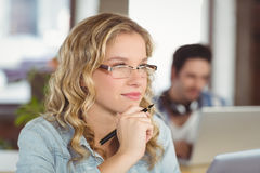 Thoughtful woman with hand on chin while colleagues working in background Stock Photo