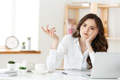 Thoughtful woman with hand under chin bored at work, looking away sitting near laptop, demotivated office worker feels. Lack of inspiration, no motivation stock image
