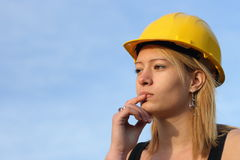 Thoughtful woman in hard hat. Royalty Free Stock Photo