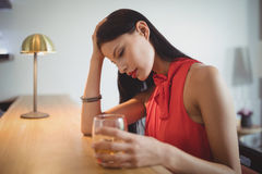 Thoughtful woman having a glass of whisky Stock Images