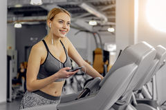 Thoughtful woman hearing song on treadmill Royalty Free Stock Photo