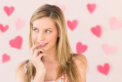 Thoughtful Woman With Heart Shaped Papers Against Colored Backgr Stock Photos