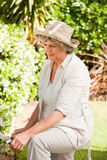 Thoughtful woman in her garden Stock Images