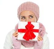 Thoughtful woman  hiding behind Christmas gift. Thoughtful woman in knit winter clothing hiding behind Christmas present box Stock Photo