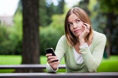 Thoughtful Woman holding Cell Phone Royalty Free Stock Image