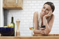 Thoughtful Woman Holding Cellphone While Leaning On Wooden Counter Royalty Free Stock Photos