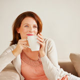 Thoughtful woman holding coffee cup on couch Stock Photography
