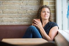 Thoughtful Woman Holding Coffee Mug In Cafe Stock Photo