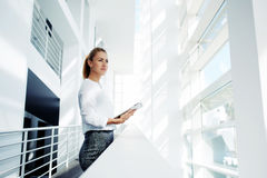 Thoughtful woman holding digital tablet and looks into the window  Stock Images