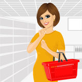 Thoughtful woman holding an empty shopping basket Stock Photography
