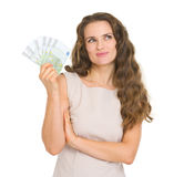 Thoughtful woman holding fun of euro banknotes Royalty Free Stock Photos