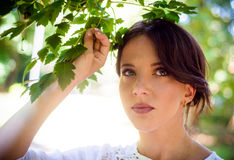 Thoughtful Woman Holding Green Leaves of a Tree Stock Photos
