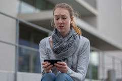 Thoughtful woman holding a mobile phone Royalty Free Stock Photography
