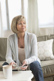 Thoughtful Woman With Holding Newspaper On Sofa Royalty Free Stock Photo